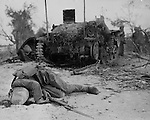 A Japanese infantryman lies srawled in front of a tank after both had been knocked out of action by U.S. Marines in their drive to the northern tip of Saipan.