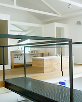 This open-plan loft apartment has a bathroom area on a platform above the kitchen which is approached by a metal walkway