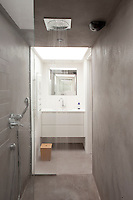 A minimal concrete shower opens into a bathroom furnished with a contemporary wash stand