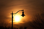 The Sun sets beneath the arch of a parkway street lamp near Lake Nokomis