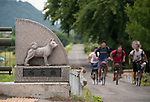 Residents pass by a carving of an Akita Inu that is part of a bridge in Odate City, Akita Prefecture Japan. The dog was formerly known as the Odate Inu. Photographer: Rob Gilhooly