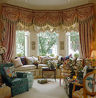Elaborate red and white curtains frame the bay window of this designer drawing room