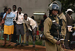 children watch as police patrol Makarere University campus as police work to restore order after student rioting broke out October, 8, 2003. Police broke up a peaceful gathering of students to discuss the current state of Ugandan politics. University officials said they did not have permission to hold the forum. the officer holds a tank of tear gas. Kalashnikov AK-47. (Rick D'Elia)