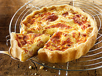 Quiche Loraine on a cooling rack with a slice being lifted