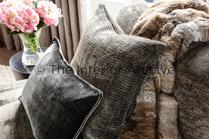 Cushions in grey tones and a fur throw are arranged on a daybed. An arrangement of pink flowers stands on a side table.