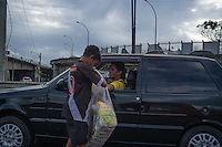 Child labor, street vendor works during rush hour traffic jam at Linha Vermelha expressway ( Red Line ), main connection between  Rio de Janeiro / Antonio Carlos Jobim International Airport and the city, Brazil - opaque hard plastic division between the highway and Favela da Mare, area dominated by drug trafficking.