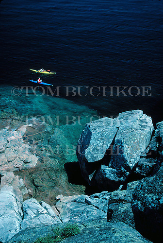 Kayakers along a rocky shore on Lake Superior