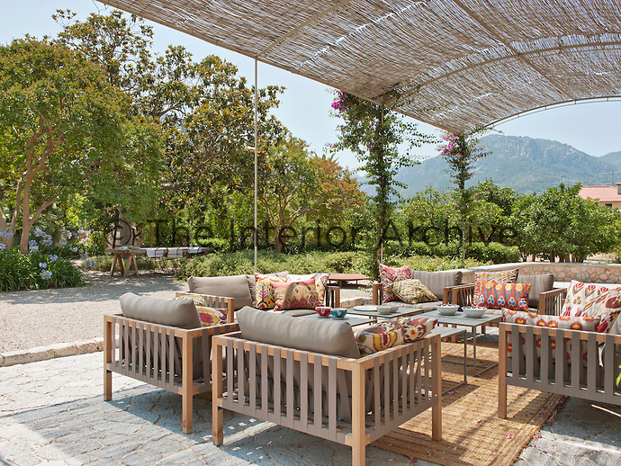Seating and tables by Damian Sanchez are arranged on an outside terrace shaded by a metal and natural cane pergola.