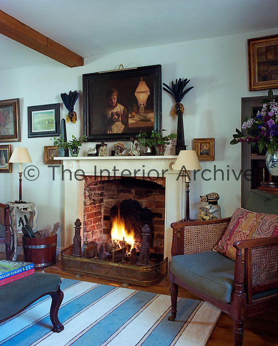 The living room is full of interesting works of art and objects including two black miniature obelisks amongst a collection of porcelain figures on the mantelpiece