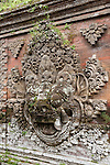 Ubud, Bali, Indonesia; stone carvings on a wall inside the Balinese Hindu temple, Pura Desa