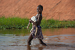 A young woman carries her goat across the river, Mopti, Mali
