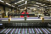 Operaia in maglia rossa lavora a macchina er tessitura Bute tartan mills