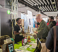 A visitor speaks with a Paydunk employee at the TechDay New York event on Thursday, April 23, 2015. Thousands attended to seek jobs with the startups and to network with their peers. TechDay bills itself as the world's largest startup event with over 300 exhibitors. (© Richard B. Levine)