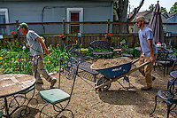 A worker uses a rope to help pull a wheelbarrow full of gravel across sections of the outdoor patio Blue Turtle Tea and Spice on East Main where the garden is being rebuilt and expanded.
