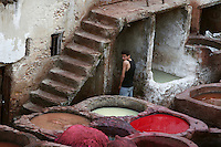 Detail of dyeing pits with a young boy in the background by the stone stairway, Chouara Tannery, Fez, Morocco, pictured on February 25, 2009 in the evening. The Chouara tannery is the largest of the four ancient tanneries in the Medina of Fez where the traditional work of the tanners has remained unchanged since the 14th century. It is composed of numerous dried-earth pits where raw skins are treated, pounded, scraped and dyed. Tanners work in vats filled with various coloured liquid dyes derived from plant sources. Colours change every two weeks, poppy flower for red, mint for green, indigo for blue, chedar tree for brown and saffron for yellow. Fez, Morocco's second largest city, and one of the four imperial cities, was founded in 789 by Idris I on the banks of the River Fez. The oldest university in the world is here and the city is still the Moroccan cultural and spiritual centre. Fez has three sectors: the oldest part, the walled city of Fes-el-Bali, houses Morocco's largest medina and is a UNESCO World Heritage Site;  Fes-el-Jedid was founded in 1244 as a new capital by the Merenid dynasty, and contains the Mellah, or Jewish quarter; Ville Nouvelle was built by the French who took over most of Morocco in 1912 and transferred the capital to Rabat. Picture by Manuel Cohen.
