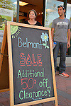 Garden City, New York, U.S. - June 6, 2014 -  ANTHONY RANDOLPHI of Valley Stream, on staff at New York Running Co, is by a chalkboard easel sign announcing the store's Belmont Sale, during the 17th Annual Garden City Belmont Stakes Festival, celebrating the 146th running of Belmont Stakes at nearby Elmont the next day. There was street festival family fun with live bands, food, pony rides and more, and a main sponsor of this Long Island night event was The New York Racing Association Inc.