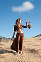 Unique woman holding a lamp in the desert.
