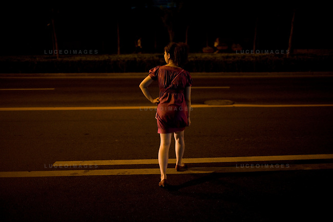 A woman tries to flag down a taxi in the late evening in Beijing, China on Thursday, August 7, 2008. There have been a taxi shortage in Beijing during the Olympics because so many more locals are only allowed to drive their personal vehicles every other day. The city of Beijing is gearing up for the opening ceremonies of the Olympic Games.  Kevin German