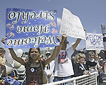In the excitement seeing the USS Rainier in the channel as she retuns to Naval Sation Bremerton, Chanthy Strehlo, left, holds her welcome home sign upside down while Bob Barcus, holds up rightside up on Monday, June 2, 2003 at Naval Station Bremerton, Wash. The two were amongst the thousand or so family members and friends who welcomed the the USS Rainier and it's crew home from deployment. Jim Bryant/AP Photo)