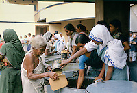 Nuns serving rice to women collecting food aid at Mother Teresa's Mission for the Poor in Calcutta, India