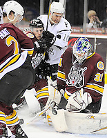 Chicago Wolves goaltender Eddie Lack (31) makes a save as San Antonio Rampage's Jon Matsumoto, center, and Chicago's Jordan Schroeder race to the puck during the second period of an AHL hockey game, Wednesday, April 4, 2012, in San Antonio. (Darren Abate/pressphotointl.com)