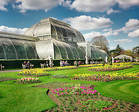 Tourists sit outside the Palm House by flower beds at the Royal Botanical Gardens, Kew in London.