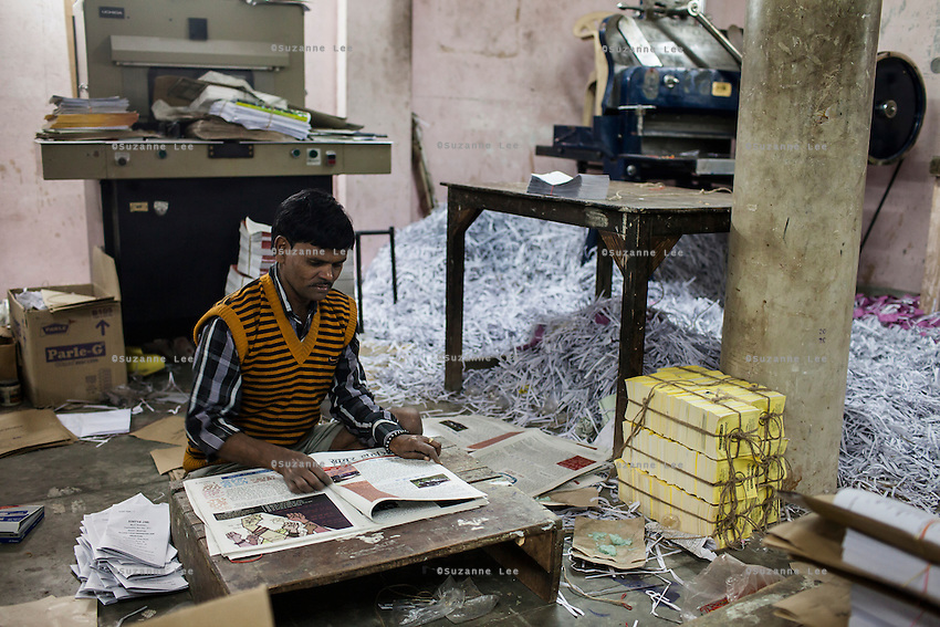Workers fold the current issue of Khabar Lahariya weekly newspaper, after receiving the files from the newspaper's Chitrakoot office, in Allahabad, Uttar Pradesh, India on 06 December 2012. Photo by Suzanne Lee / Marie Claire France