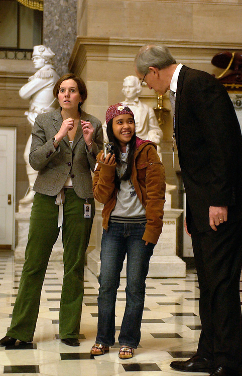 Thuy Anh, center, a student sponsored by Chief of Staff for Rep. Bart Gordon, D-Tenn., right, listens for people talking across the room with staffer Katie Dawson in Statuary Hall during a Capitol tour.