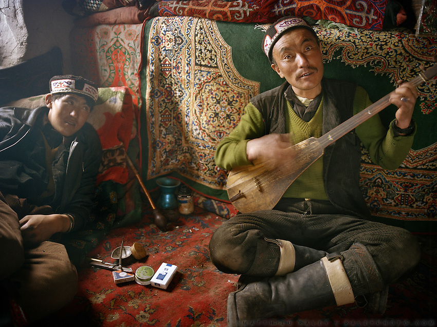 Ooroon Boi, high on opium, sings with a Komuz..Opium users inside Ooroon Boi's house, son of the Khan. Winter expedition through the Wakhan Corridor and into the Afghan Pamir mountains, to document the life of the Afghan Kyrgyz tribe. January/February 2008. Afghanistan
