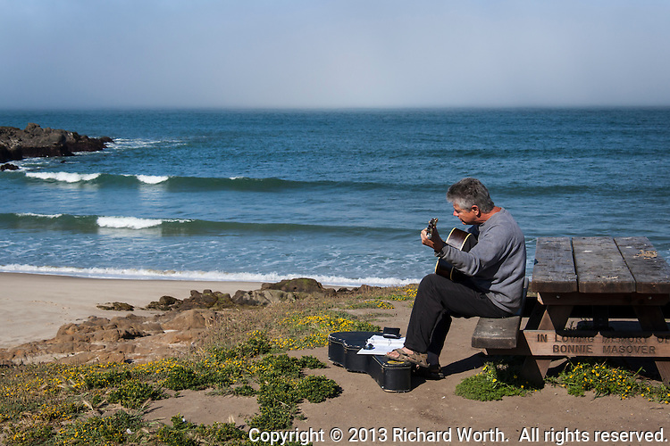Visitor Doug Vanderberg, plays his guitar while gentle waves roll in to Bean Hollow State Beach,