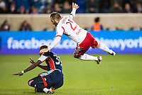 Brandon Barklage (25) of the New York Red Bulls flies over Saer Sene (39) of the New England Revolution. The New York Red Bulls defeated the New England Revolution 4-1 during a Major League Soccer (MLS) match at Red Bull Arena in Harrison, NJ, on March 20, 2013.