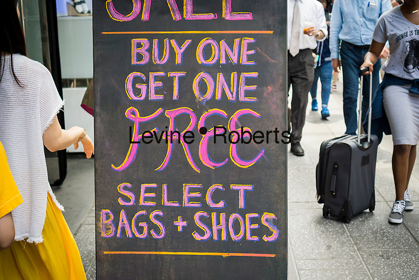 "A ""buy one, get one"" promotion advertised outside of a clothing store in New York on Friday, June 17, 2016.  (© Richard B. Levine)"