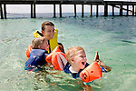 Singaporean Alexa Croly-Labourdette plays with her twin sons, Niels and Emile, 2, along the shore of Nikoi, a private resort island in Indonesia, on Monday, April 19, 2010.