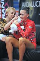 "Anna Alyabyeva of Kazakhstan smiles receiving rabbit doll from coach at ""kiss & cry""  during event finals  at 2010 Grand Prix Marbella at San Pedro Alcantara, Spain on May 16, 2010. Anna placed 6th AA at Marbella 2010. (Photo by Tom Theobald)."