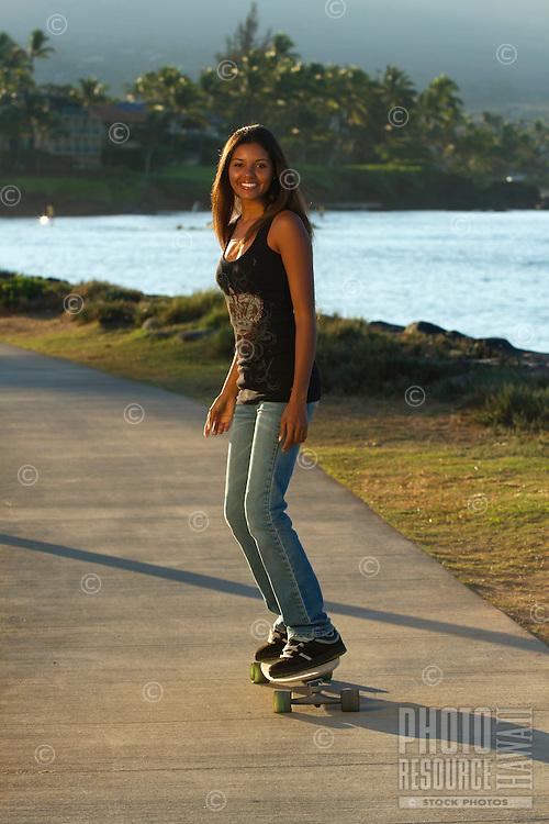 A beautiful, healthy young woman rides a skateboard in Kihei, Maui.