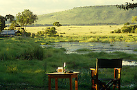 A bottle of beer on a side table next to a director's chair, both positioned in a perfect spot for a sun downer overlooking a water hole
