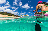 A young woman paddles a Hawaiian outrigger canoe off of Sunset Beach, on O'ahu's North Shore.