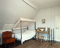This modest servant's bedroom features a single four-poster bed tucked under the sloping attic ceiling with a wash basin and water pitcher on a simple washstand