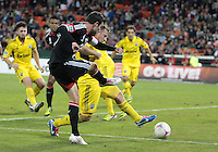 WASHINGTON, DC - OCTOBER 20, 2012:  Chris Pontius (13) of D.C United sends a cross past Chris Birchall (8) of the Columbus Crew during an MLS match at RFK Stadium in Washington D.C. on October 20. D.C United won 3-2.