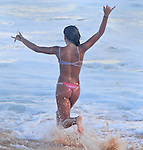 A young girls runs for the ocean at Sandy Beach in Hawaii during high-tide.