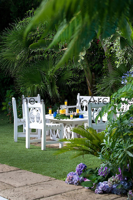 White garden furniture has been designed with a motif of a palm tree