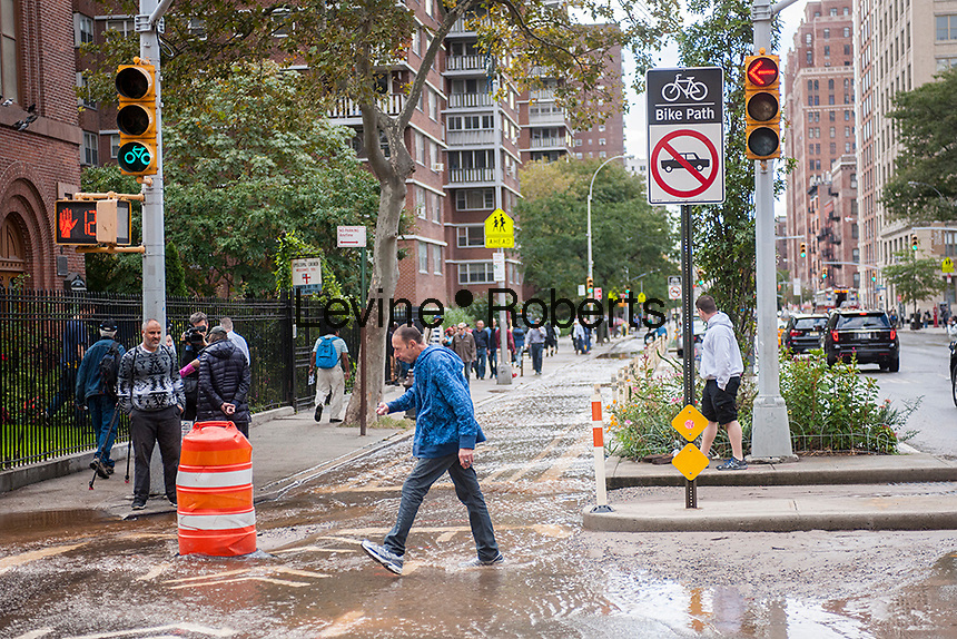 Pedestrians maneuver through flowing water from a watermain break  in the Chelsea neighborhood of New York on Wednesday, October 12, 2016. The watermain break caused water to gush but it was mostly contained to the street safely running into storm drains. (© Richard B. Levine)