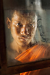 _DSC8513, Thailand, 2007, THAILAND-10025. A monk peers out of a window.<br />