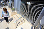 Palestinians walk passed closed doors of Jawwal headquarter in Gaza City on June 30, 2015. Palestinian police in Gaza closed of Jawwal headquarter this morning by order attorney general in Gaza strip. Photo by Mohammed Asad