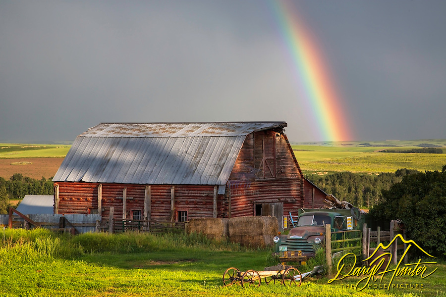 Old truck, rainbow, log barn