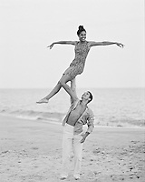 Man holding woman up with one hand on the beach