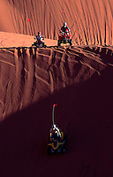 Freewheeling four-wheelers ride over the Coral Pink Sand Dunes of southwestern Utah. Part state park, part BLM wilderness-quality land, the dunes are both playground and battleground. ATVers fight for wide-open access; environmentalists for rare plant and animal species.....The park's sand dunes, some measuring several hundred feet high, are created because a notch between the Moquith and Moccasin mountains funnels the prevailing winds, increasing their velocity to a point where they can carry sand grains in what is called the Venturi Effect. Eroding Navajo Sandstone formations surrounding the park account for the unique color of these dunes.