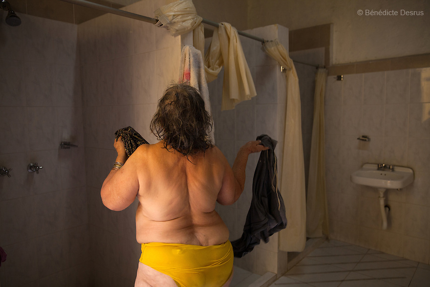 Amalia, a resident of Casa Xochiquetzal, takes a shower at the shelter in Mexico City, Mexico on October 2, 2013. Amalia, 66, is from Michoacán and came to Casa Xochiquetzal when it first opened its doors. She wears a wig and pads her bra. She is very animated; words and songs come easily to her. She has also suffered from schizophrenia for 22 years, but despite hearing voices, she works hard not to lose touch with reality. As a way of earning a little money, she gathers plastic bottles to recycle and also helps to sell clothes in a stand operated by her boyfriend of 31 years. Casa Xochiquetzal is a shelter for elderly sex workers in Mexico City. It gives the women refuge, food, health services, a space to learn about their human rights and courses to help them rediscover their self-confidence and deal with traumatic aspects of their lives. Casa Xochiquetzal provides a space to age with dignity for a group of vulnerable women who are often invisible to society at large. It is the only such shelter existing in Latin America. Photo by Bénédicte Desrus
