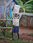 A boy carries water as he walks through Mizak, a small village in the south of Haiti.