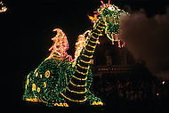 Orlando, Florida - Circa 1986. Disney character 'The Reluctant Dragon' breathes smoke at the audience at the Main Street Electrical Parade. The Main Street Electrical Parade was created by Bob Jani and Ron Miziker, and first appeared at Disney World on June 11, 1977. Disney World is a world-renowned entertainment complex that opened October 1, 1971 in Lake Buena Vista, FL. Now known as the Walt Disney World Resort, the property covers 25,000 acres and has an annual attendance of 52.5million people.